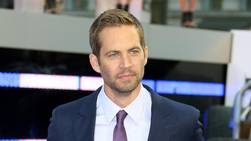 "FILE - In this May 7, 2013 file photo, actor Paul Walker arrives for the World Premiere of ""Fast & Furious 6,"" in central London. Wiz Khalifa and Charlie Puth's song, ""See You Again,"" a tribute to Walker, hit No.1 on Billboard Hot 100's chart this week. It is featured on the ""Furious 7"" soundtrack, which debuted at No.1 on Billboard's 200 albums chart this week. (Photo by Joel Ryan/Invision/AP)"