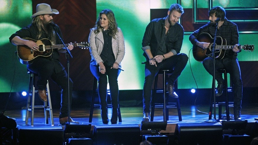 Chris Stapleton, left, performs with Hillary Scott, Charles Kelley, and Dave Haywood of Lady Antebellum at the CMT Artist of the Year Awards at the Schermerhorn Symphony Center on Tuesday, Dec. 2, 2014, in Nashville, Tenn.