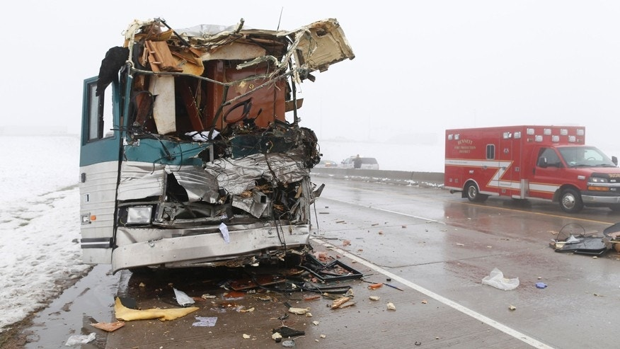 A tour bus involved in an accident with a tractor trailer sits on the shoulder of the westbound lanes of Interstate 70 Friday, April 17, 2015, in Aurora, Colo.