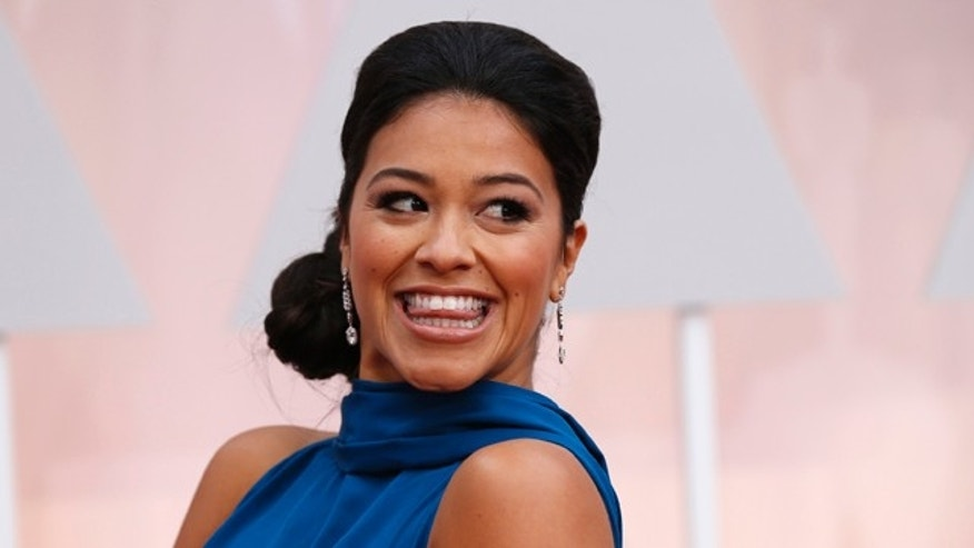 February 22, 2015. Actress Gina Rodriguez, wearing a bright blue Manon Gabard gown, arrives at the 87th Academy Awards in Hollywood, California.