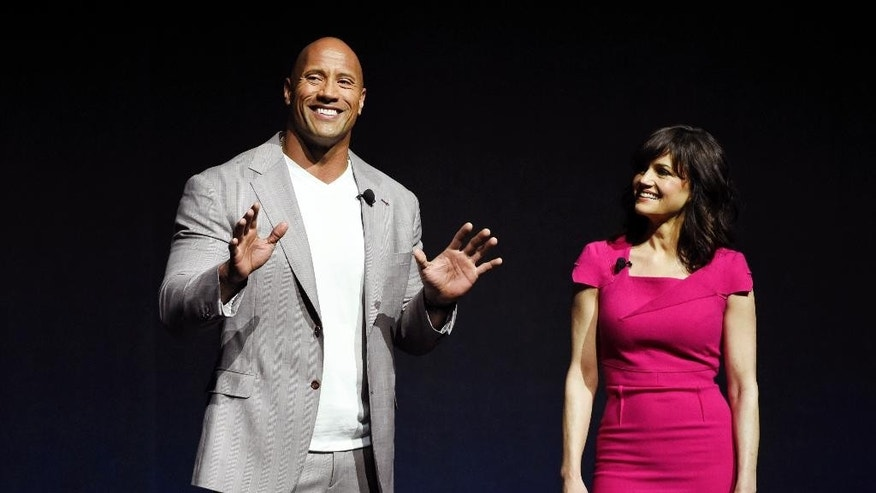 "FILE - In this Tuesday, April 21, 2015 file photo, Dwayne Johnson, left, a cast member in the upcoming film ""San Andreas,"" and fellow cast member Carla Gugino introduce a clip from the film during CinemaCon 2015 at Caesars Palace, in Las Vegas. Warner Bros. will evaluate the worldwide marketing campaign for its upcoming earthquake film ""San Andreas"" in light of the Nepal earthquake, the studio said Wednesday, April 29, 2015.  (Photo by Chris Pizzello/Invision/AP, File)"