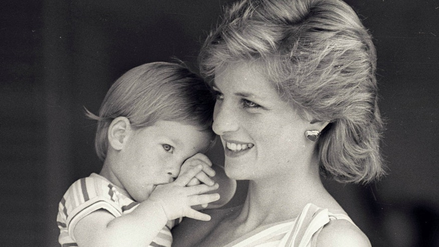 August 9, 1988. Young Prince Harry tries to hide behind his mother Princess Diana during a morning picture session at Marivent Palace.