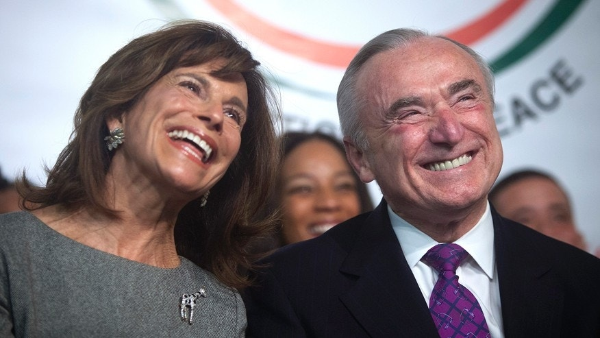 December 7, 2013. Newly appointed New York City Police Commissioner William Bratton and wife Rikki Klieman listen during a tribute service for Nelson Mandela at the National Action Network's headquarters in the Harlem area of New York.