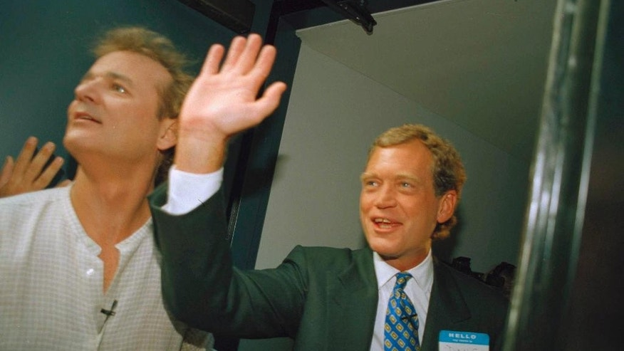 """FILE - In this Aug. 30, 1993 file photo, David Letterman, right, and Bill Murray wave from the side door of the Ed Sullivan Theater during the first episode of """"Late Show with David Letterman"""" in New York. After 33 years in late night and 22 years hosting CBS' """"Late Show,"""" Letterman will retire on May 20. (AP Photo/Jim Cooper)"""