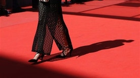 An unidentified guest walks on the red carpet as she arrives for the screening of the film La Loi du Marche (The Measure of a Man) at the 68th international film festival, Cannes, southern France, Monday, May 18, 2015. (AP Photo/Lionel Cironneau)