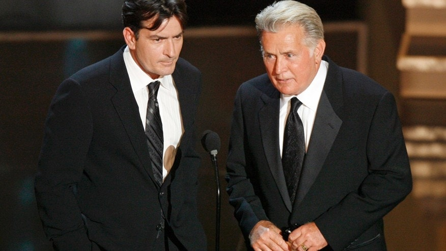 Charlie Sheen (L) and his father Martin Sheen present the best supporting actress in a miniseries or movie award during the 58th annual Primetime Emmy Awards at the Shrine Auditorium in Los Angeles August 27, 2006.