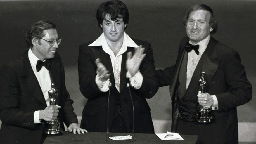 FILE - In this Jan. 30, 1977, file photo, 'Rocky' co-producers Irwin Winkler, left, and Robert Chartoff, right, flank Sylvester Stallone after receiving Golden Globes at the 34th Annual Golden Globe Awards in Los Angeles. (AP Photo/File)