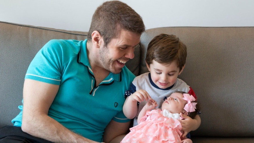 This Sunday, June 7, 2015 photo shows, Perez Hilton, from left, his son Mario, and his new daughter Mia posing for a portrait at the Sofitel, in New York. Hiltonâs first Fatherâs Day with his baby girl will be on Sunday, June 21. The 37-year-old celebrity blogger (real name: Mario Lavanderia) started his family in 2013 when son Mario was born via surrogate. (Photo by Amy Sussman/Invision/AP)(Photo by Amy Sussman/Invision/AP)