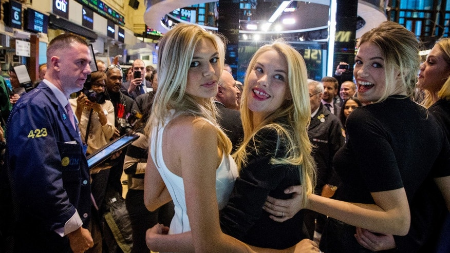 Sports Illustrated swimsuit models Kelly Rohrbach, Ashley Smith (2nd R), and Hailey Clauson (R) pose together on the floor of the New York Stock Exchange, February 6, 2015. REUTERS/Brendan McDermid (UNITED STATES - Tags: BUSINESS FASHION) - RTR4OK0G