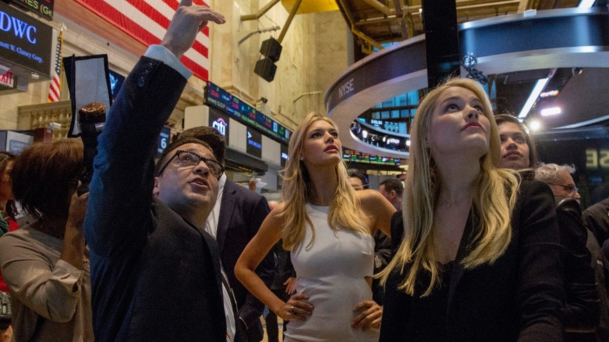Sports Illustrated swimsuit models Kelly Rohrbach (C) and Ashley Smith (R) are given a tour of the floor of the New York Stock Exchange February 6, 2015. REUTERS/Brendan McDermid (UNITED STATES - Tags: BUSINESS FASHION) - RTR4OK6Y