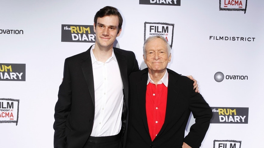 "October 13, 2011. Playboy magazine founder Hugh Hefner (R) and son Cooper arrive at the premiere of the film ""The Rum Diary"" in Los Angeles."