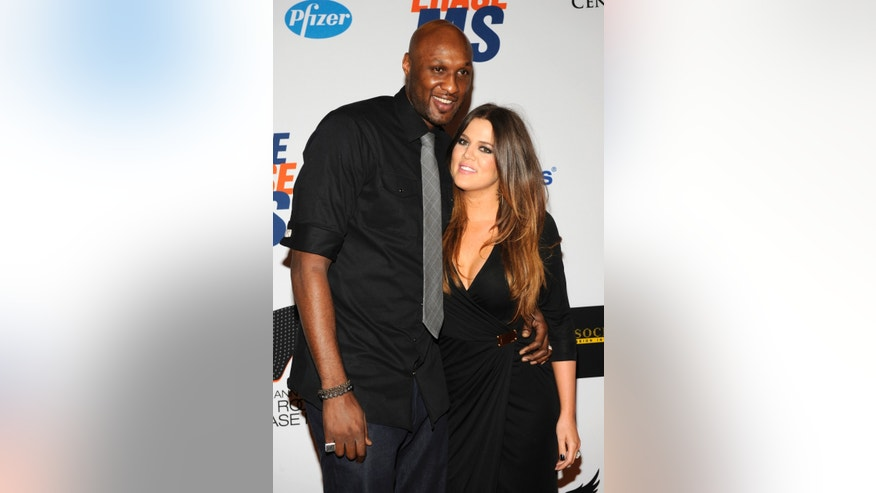 Lamar Odom (L), basketball player with the Dallas Mavericks of the NBA, and his wife Khloe Kardashian-Odom arrive for the 19th annual Race to Erase MS Gala in Los Angeles May 18, 2012. REUTERS/Phil McCarten (UNITED STATES - Tags: ENTERTAINMENT SPORT BASKETBALL) - RTR32A3E