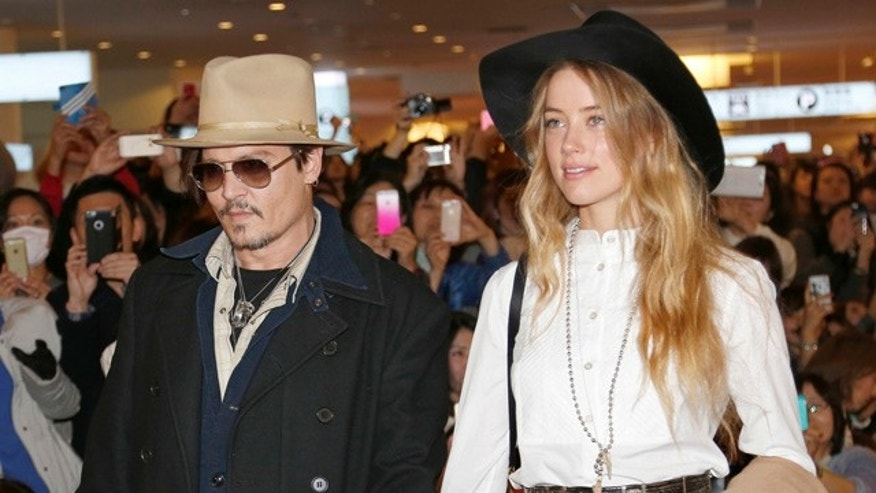 FILE - In this Jan. 26, 2015 file photo, U.S. actor Johnny Depp and Amber Heard arrive at Haneda international airport in Tokyo to promote his latest film 'Mortdecai'. Heard has been charged with illegally bringing the couple's dogs to Australia. Prosecutors on Thursday, July 16, 2015 said that Heard was charged this week with two counts of illegally importing Pistol and Boo into Australia and one count of producing a false document. (AP Photo/Shizuo Kambayashi, File)