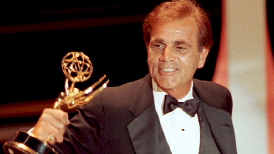 Actor Alex Rocco holds up his 1990 Emmy award for best supporting actor in a television comedy series.