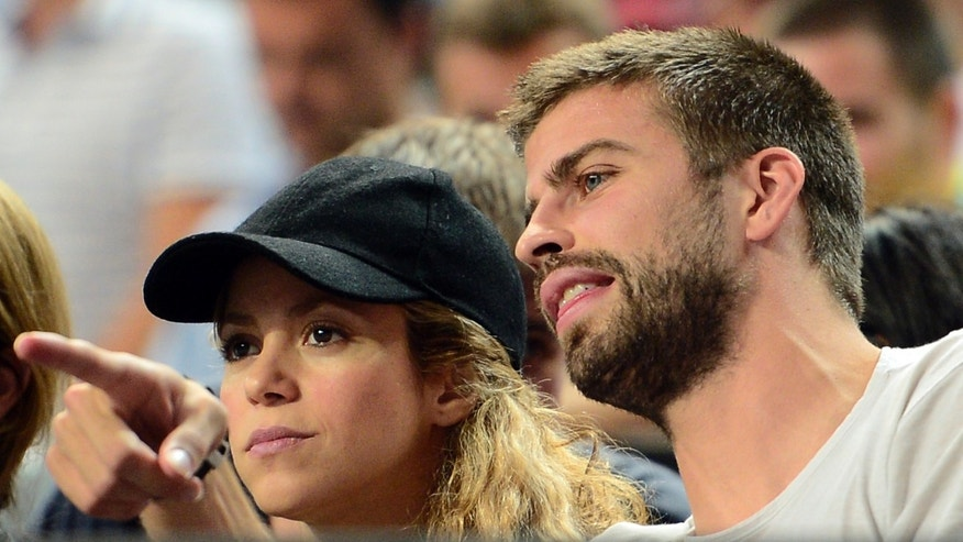 FC Barcelona's player Gerard Pique, right, and Colombian singer Shakira attend a Basketball World Cup quarterfinal match between Slovenia and United States at the Palau Sant Jordi in Barcelona, Spain, Tuesday, Sept. 9, 2014. The 2014 Basketball World Cup competition will take place in various cities in Spain from Aug. 30 through to Sept. 14. (AP Photo/Manu Fernandez)