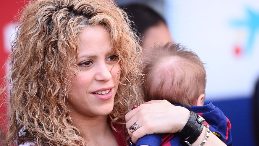 "FILE - In this April 18, 2015 file photo, Colombian singer Shakira holds her son Sasha prior to a Spanish La Liga soccer match between FC Barcelona and Valencia at the Camp Nou stadium in Barcelona, Spain. On Wednesday, July 29, Shakira posted on Twitter and Facebook a video titled ""Happy 6 months Sasha!"" in which she appears holding Sasha in front of a soccer ball. The child raised his leg and gently kicked the ball. (AP Photo/Manu Fernandez, File)"