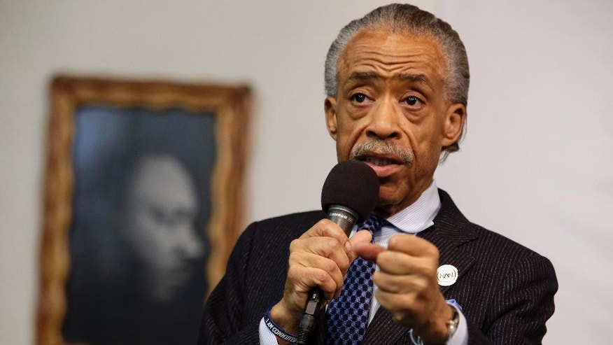 "FILE - In this May 2, 2015 file photo, a portrait of the Rev. Dr. Martin Luther King Jr. hangs on the wall behind the Rev. Al Sharpton as he speaks during a rally at the National Action Network, in New York. Sharpton is losing his daily show on MSNBC, with the network saying Wednesday, Aug. 26, 2015, that he'll be downshifted to the weekend. Sharpton's ""Politics Nation"" aired on weeknights at 6 p.m. EDT for the past four years at the ratings-challenged news network  (AP Photo/Mary Altaffer, File)"