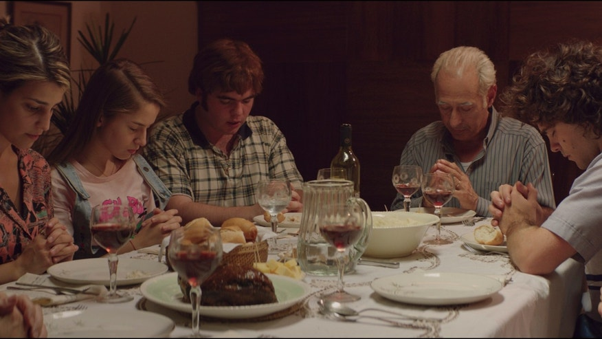 In this undated film frame released by K&S Films, actors playing the members of Puccio pray before dinner during the film The Clan by Argentine filmmaker Pablo Trapero. Over the course of about three years, members of the family killed at least three people they had kidnapped for ransom. A fourth victim was freed after being held in chains in a basement cell of the Puccio home. (K&S Films via AP)