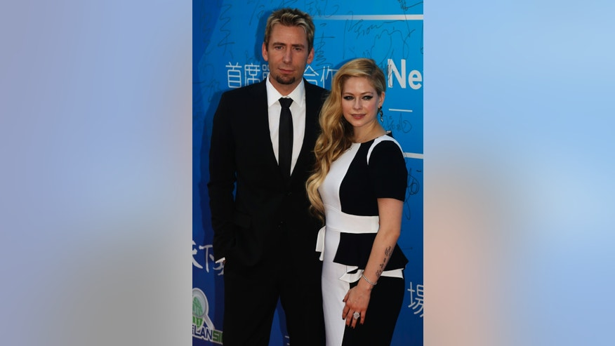 October 7, 2013. Canadian singer and songwriter Avril Lavigne and her husband Chad Kroeger pose on the red carpet at the Huading Awards ceremony in Macau.