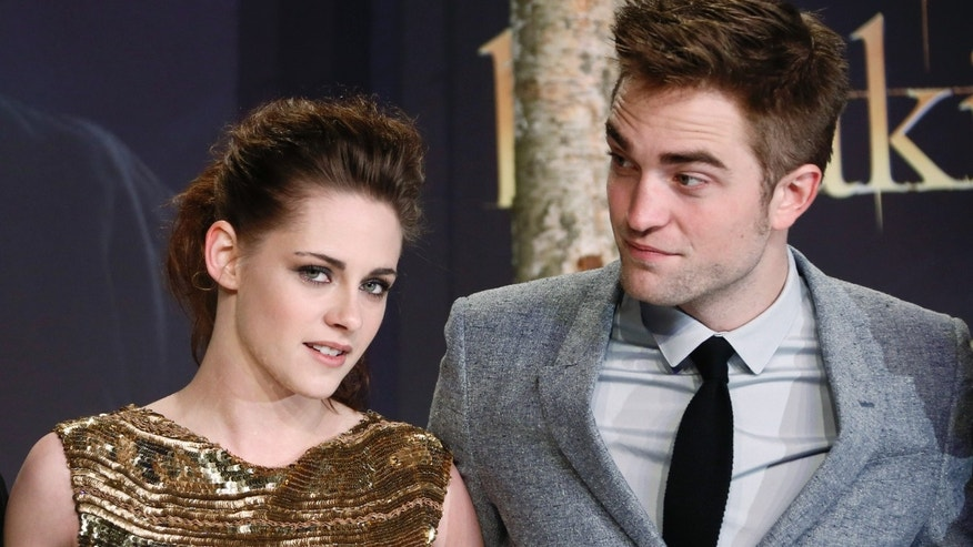 Cast members Robert Pattinson (R) and Kristen Stewart pose for pictures before the German premiere of The Twilight Saga: Breaking Dawn Part 2 in Berlin, November 16, 2012.   REUTERS/Thomas Peter (GERMANY - Tags: ENTERTAINMENT) - RTR3AI1Q