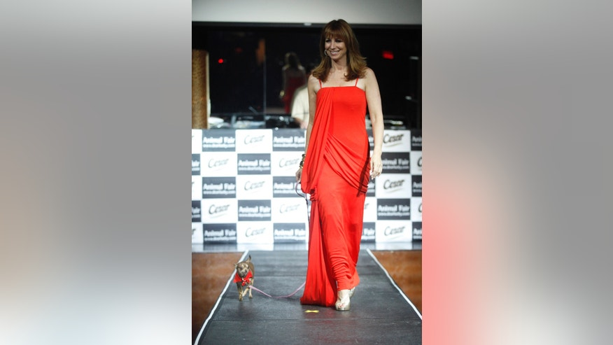 """July 27, 2009. Reality television personality Jill Zarin walks on the runway with her dog Darren during the """"Paws for Style"""" dog fashion show in New York."""