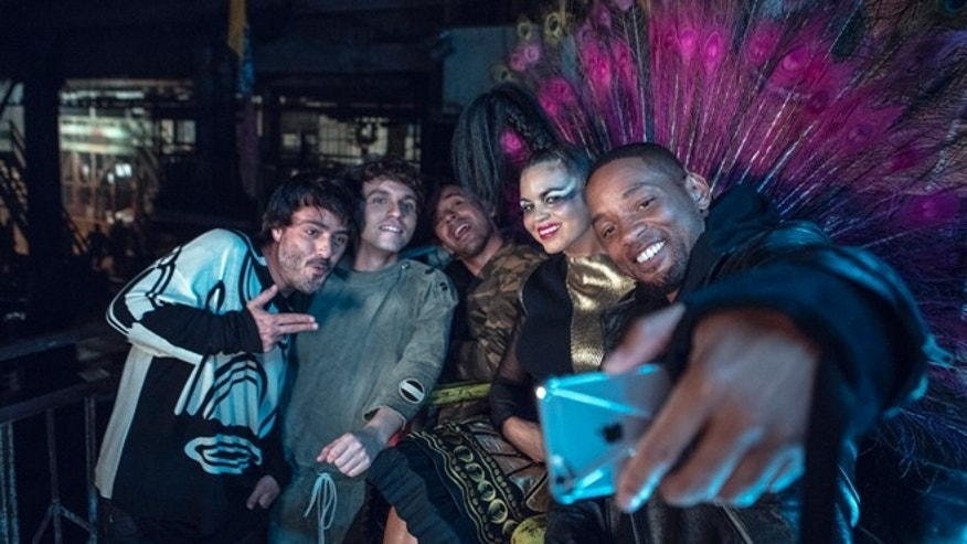 In this Sept. 17, 2015 photo released by Sony Music, members of Bomba Estereo, from left, Simon Mejia, Julian Salazar, Andres Zea and Liliana Saumet pose for a selfie with actor-singer Will Smith, who appears on a remix to Colombian band Bomba Estereos song, Fiesta. The remix was released digitally Friday, Oct. 2. The collaboration marks Smiths return to music since his 2005 album, Lost and Found. Smith discovered Bomba Estereo, known for its blend of Latin, tropical and electro sounds, on a recent trip to Colombia. He then asked the group to collaborate. (Alan Silfen/Sony via AP)