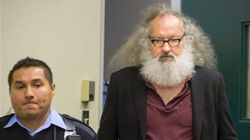 Actor Randy Quaid is escorted into his Immigration and Refugee Board hearing in Montreal, Thursday, Oct. 8, 2015. (Peter McCabe/The Canadian Press via AP)