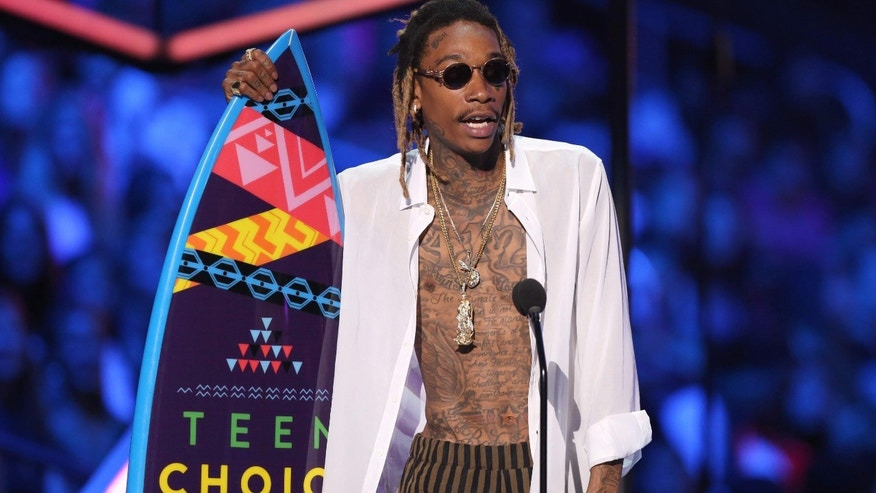 "FILE - In this Aug. 16, 2015, file photo, Wiz Khalifa accepts the choice R&B/hip-hop song award for ""See You Again"" at the Teen Choice Awards at the Galen Center in Los Angeles."