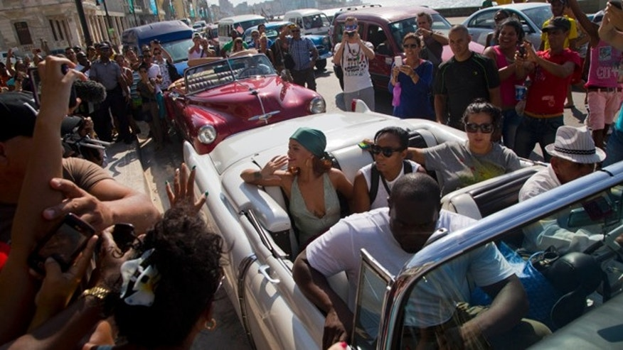 FILE - In this May 29, 2015, file photo, fans take photographs of pop artist Rihanna, wearing a green scarf, as she is transported in an American classic car, after a photo shoot with photographer Annie Leibovitz at a building on the Malecon, in Havana, Cuba. This October's Vanity Fair has Rihanna on the cover in Havana as celebreties keep flocking to Havana. Mick Jagger and Katy Perry have partied (separately) here over the last week. Mexico City's hottest chef is scoping sites for a Havana restaurant. Usher and Ludacris have shown up. Jimmy Buffet's played a private backyard concert for friends. (AP Photo/Desmond Boylan, File)