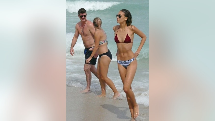 Robin Thicke (left) was pictured as he swam in the ocean with his son Julian, a friend (center) and long time girlfriend April Love Geary (right) while in Miami Beach.
