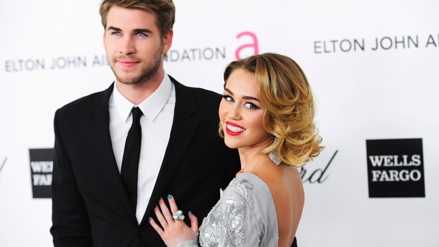 Singer Miley Cyrus (R) and actor Liam Hemsworth arrive at the 20th annual Elton John AIDS Foundation Academy Awards Viewing Party in West Hollywood, California February 26, 2012.