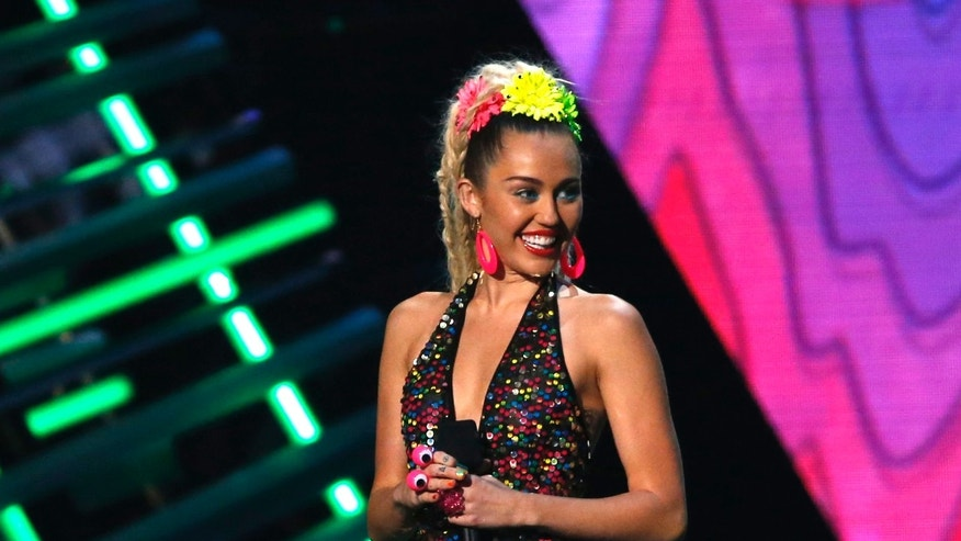 August 30, 2015. Show host Miley Cyrus speaks on stage at the 2015 MTV Video Music Awards in Los Angeles, California.