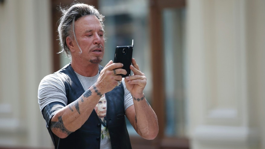 Actor Mickey Rourke wears a T-shirt with an image depicting Russia's President Vladimir Putin, as he snaps a photograph at GUM department store in central Moscow, August 11, 2014. Creators of the new T-shirt collection, which went on sale Monday after an earlier batch sold in June was well-received, produced the T-shirts displaying images of Russia's President Putin as they were inspired by triumphs of Russian sportsmen at the Sochi 2014 Olympics, the Paralympic Winter Games and the 2014 Men's Ice Hockey World Championship, as well as Russia's annexation of Crimea, according to local media. REUTERS/Maxim Zmeyev (RUSSIA - Tags: SOCIETY POLITICS FASHION BUSINESS ENTERTAINMENT) - RTR41YZM