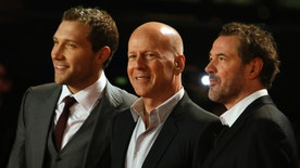 "Actors (L-R) Jai Courtney, Bruce Willis and Sebastian Koch pose for photographers as they arrive for the British Premiere of ""A Good Day to Die Hard"" at Leicester Square in London February 7, 2013.  REUTERS/Luke MacGregor  (BRITAIN - Tags: ENTERTAINMENT SOCIETY) - RTR3DH1G"