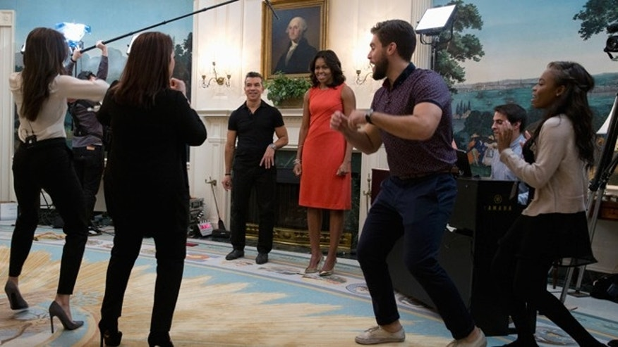 First lady Michelle Obama stands with Colombian dancer and choreographer Sergio Trujillo, third from left, as Ana Villafañe, left, Gloria Estefan, second from left and Josh Segarra third from right, dance for her in the Diplomatic Room of the White House in Washington, Monday, Nov. 16, 2015, during a Broadway at the White House event for high school students involved in performing arts programs. (AP Photo/Carolyn Kaster)
