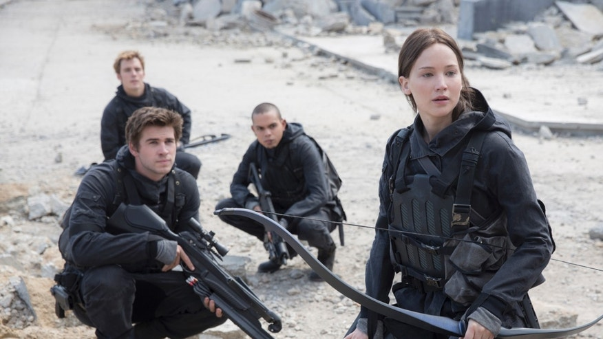 "Liam Hemsworth, left, as Gale Hawthorne, Sam Clafin, back left, as Finnick Odair, Evan Ross, back right, as Messalia, and Jennifer Lawrence, right, as Katniss Everdeen, in the film, ""The Hunger Games: Mockingjay - Part 2."""