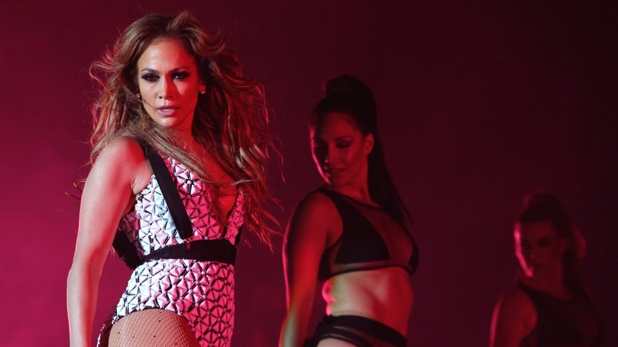 FILE - In this May 29, 2015, file photo, Jennifer Lopez performs on stage at Morocco's biggest music Mawazine Festival in Rabat, Morocco. The American Music Awards on Sunday, Nov. 22, 2015, hosted by Lopez, will feature performers, Justin Bieber, One Direction, Carrie Underwood, Coldplay, Ariana Grande, Selena Gomez, Gwen Stefani and Luke Bryan. One Direction is nominated for artist of the year, pitting them against Grande, Bryan, Nicki Minaj and Taylor Swift. (AP Photo/Abdeljalil Bounhar, File)
