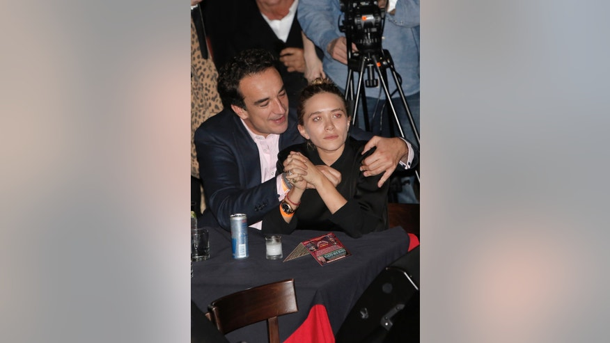 November 7, 2013. Half-brother of former French President Nicolas Sarkozy, Olivier Sarkozy (L) and girlfriend actress Mary-Kate Olsen (R) watch Rolling Stones guitarist Ronnie Wood play at The Cutting Room in New York.