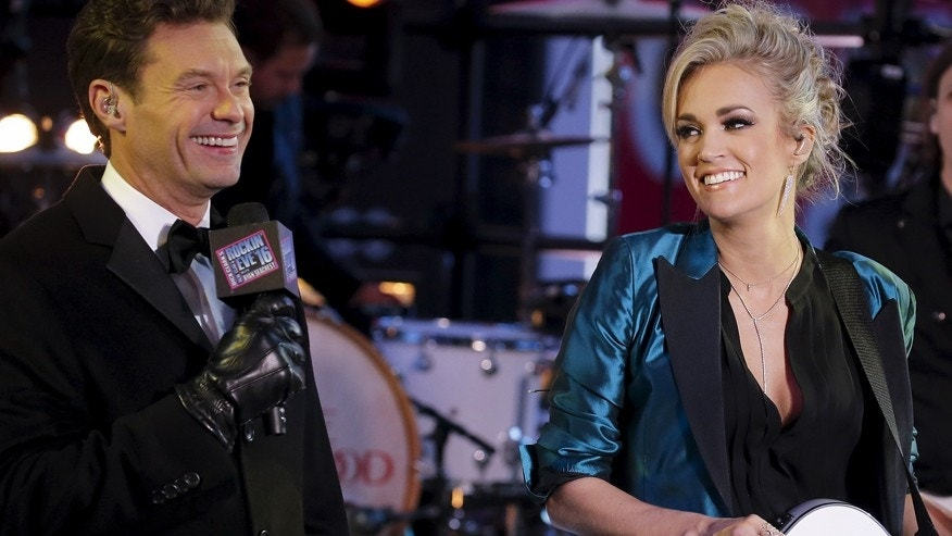 TV host Ryan Seacrest (L) introduces Singer Carrie Underwood on the main stage in Times Square during New Year's Eve celebrations in the Manhattan borough of New York, December 31, 2015.    REUTERS/Carlo Allegri - RTX20OYT