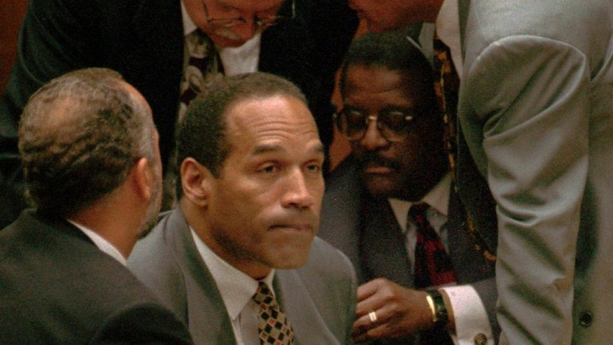 "FILE - In this Aug. 29, 1995, file photo, O.J. Simpson, second from left, is surrounded by his attorneys, clockwise from left, Ken Spaulding, back towards camera, Gerald Uelmen, Robert Shapiro and Johnnie Cochran Jr., as they discuss their plans for arguing the admissibility of the tapes of retired Los Angeles police detective Mark Fuhrman in Los Angeles. A lawyer for O.J. Simpson in Las Vegas says the imprisoned former football star isn't happy with portrayals he's seen in ads and interviews about a cable TV series focusing on his 1995 murder acquittal in Los Angeles. Simpson won't be able to see the show, ""The People v. O.J. Simpson,"" as Nevada prisons don't carry the FX network, which debuts the 10-part show on Tuesday, Feb. 2, 2016. (Myung J. Chun/Los Angeles Daily News via AP, Pool, File)"