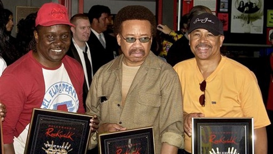 In this July 7, 2003 file photo, Philip Bailey, from left, Maurice White, and Ralph Johnson, of Earth Wind & Fire hold up the plaques from their induction at the Hollywood Rock Walk at a ceremony in Los Angeles.
