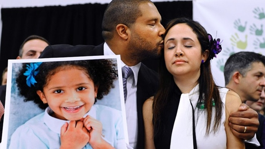 FILE - In this Jan. 14, 2013 file photo, Jimmy Greene, left, kisses his wife Nelba Marquez-Greene as he holds a portrait of their daughter, Sandy Hook School shooting victim Ana Marquez-Greene, at a news conference in Newtown, Conn., Monday, Jan. 14, 2013. Jimmy Greene, an internationally acclaimed jazz saxophonist, composer and bandleader, is preparing an album, called âA Beautiful Life,â inspired by his daughter. He plans to play selections from the album Sunday, Aug. 10, 2014 at the Litchfield, Conn., Jazz Festival. (AP Photo/Jessica Hill, File)