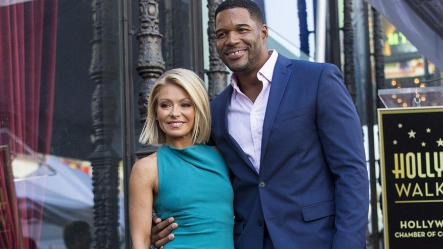 Television personality Kelly Ripa poses on her star with former professional American football player Michael Strahan after it was unveiled on the Hollywood Walk of Fame in Los Angeles, California October 12, 2015.  REUTERS/Mario Anzuoni - RTS4654