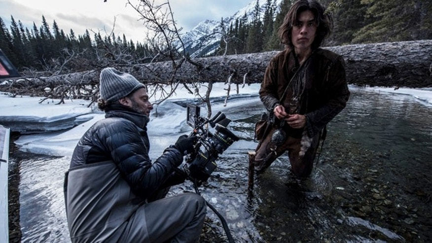 "This photo provided by courtesy of Twentieth Century Fox shows, cinematographer Emmanuel Lubezki , left, and Forrest Goodluck as Hawk on set for the film, ""The Revenant,"" directed by Alejandro Gonzalez Inarritu. No name is more feverishly celebrated in Hollywood right now than ""Chivo."" That's the nickname of the famed cinematographer Lubezki, whose acrobatic long-takes and luminous natural images of natural light have made him revered -- and may make him a three-peat Oscar winner for ""Gravity,"" ''Birdman"" and now ""The Revenant."" The Oscars will be presented on Feb. 28, 2016, in Los Angeles. (Kimberley French/Twentieth Century Fox via AP)"