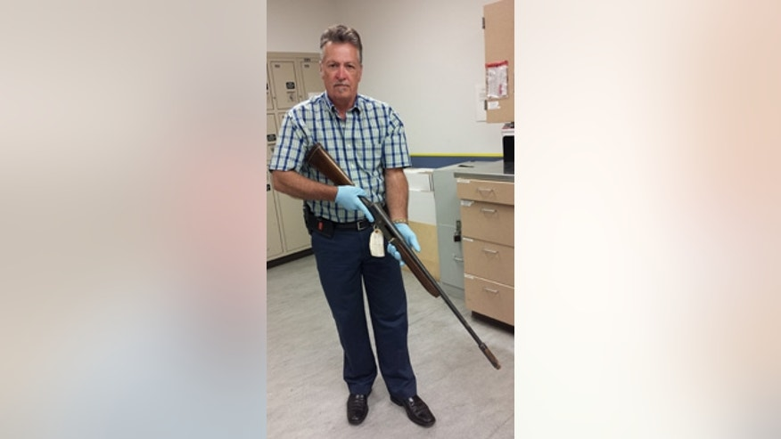 In this June 2015 photo released by the Seattle Police on Thursday, March 17, 2016, Detective Michael Ciesynski holds the shotgun which rock legend Kurt Cobain used to kill himself on April 8, 1994. (Seattle Police via AP)