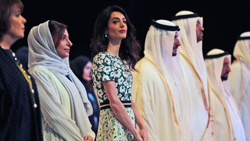 March 20, 2016. Amal Alamuddin Clooney, writer, human rights activist, 3rd left, listens to the national anthem during the opening ceremony of the International Government Communications Forum in Sharjah, United Arab Emirates.