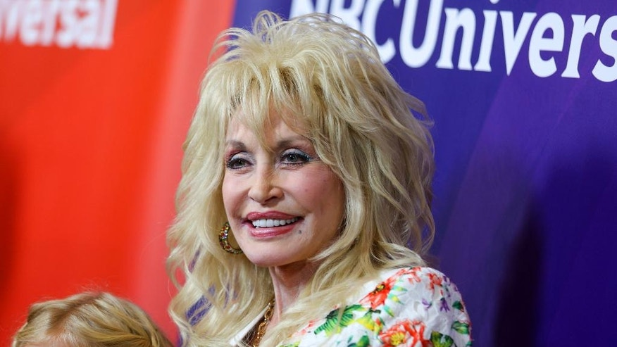 FILE - In this Aug. 13, 2015 file photo, Dolly Parton arrives at the NBCUniversal Summer TCA Tour in Beverly Hills, Calif. Parton and pop star Katy Perry will sing together at the 51st annual Academy of Country Music Awards, where Parton will be receiving a special award for her recent television movie about her childhood. The ACM Awards will air live on April 3 from the MGM Grand Garden Arena in Las Vegas on CBS. (Photo by Rich Fury/Invision/AP, File)