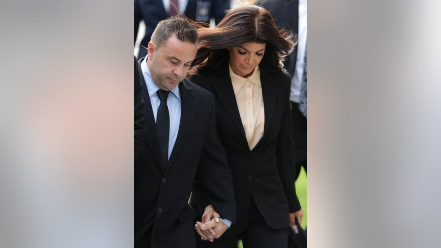 "FILE-  In this Oct. 2, 2014 file photo, ""The Real Housewives of New Jersey"" stars Teresa Giudice, and her husband Giuseppe ""Joe"" Giudice, left, of Montville Township, N.J., walk toward Martin Luther King Jr. Courthouse for a court appearance on federal conspiracy and bankruptcy fraud charges in Newark, N.J. An attorney for Joe Giudice said the husband of Teresa Giudice, is expected to report to the Fort Dix federal prison on Wednesday, March 23, 2016, to begin serving a 41-month sentence for bankruptcy fraud. (AP Photo/Julio Cortez, File)"
