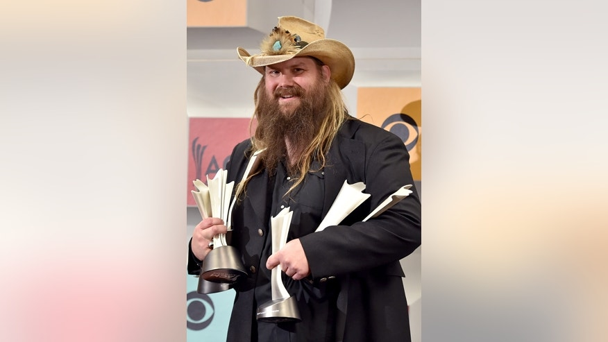 "Chris Stapleton poses in the press room with the awards for album of the year for ""Traveller"", new male vocalist of the year, male vocalist of the year and song of the year for Nobody to Blame, at the 51st annual Academy of Country Music Awards at the MGM Grand Garden Arena on Sunday, April 3, 2016, in Las Vegas."