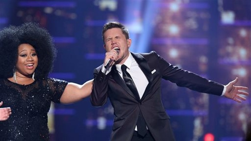 "Winner Trent Harmon, right, performs at the ""American Idol"" farewell season finale at the Dolby Theatre on Thursday, April 7, 2016, in Los Angeles. Looking on from left is La'Porsha Renae. (Photo by Matt Sayles/Invision/AP)"